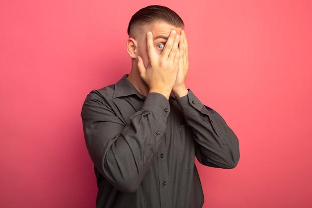 ピンクの壁の上に立っている彼の指を通して見ている手で目を覆っている灰色のシャツの若いハンサムな男