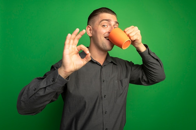 灰色のシャツを着た若いハンサムな男がコーヒーを飲みながらオレンジ色のマグカップを笑顔で緑の壁の上に立っているokサインを示しています
