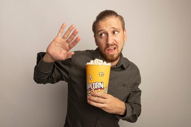 Молодой красавец в серой рубашке держит ведро с попкорном, смотрит в сторону взволнованно и смущенно, протягивая руку как защитный жест