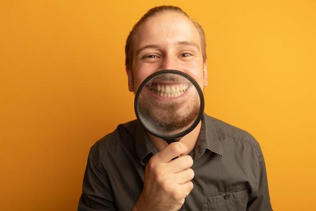 彼の歯を示す彼の大きな笑顔の前に虫眼鏡を保持している灰色のシャツを着た若いハンサムな男