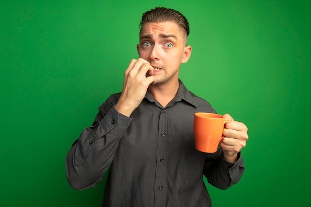 灰色のシャツを着た若いハンサムな男が正面を見てオレンジ色のマグカップを持ってストレスを感じ、緑の壁の上に立っている彼の爪を神経質に噛む