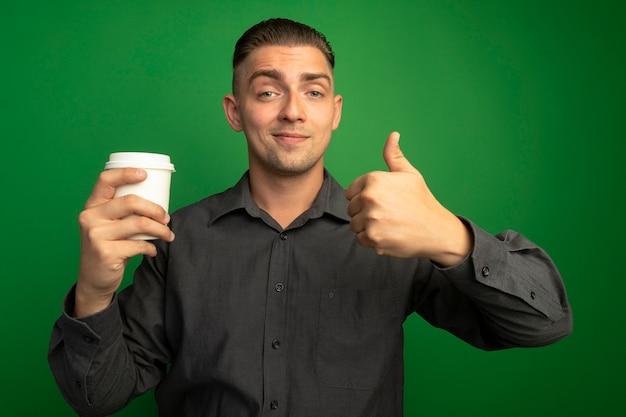 녹색 벽 위에 서 엄지 손가락을 보여주는 전면 smilign 자신감을 찾고 종이 컵을 들고 회색 셔츠에 젊은 잘 생긴 남자