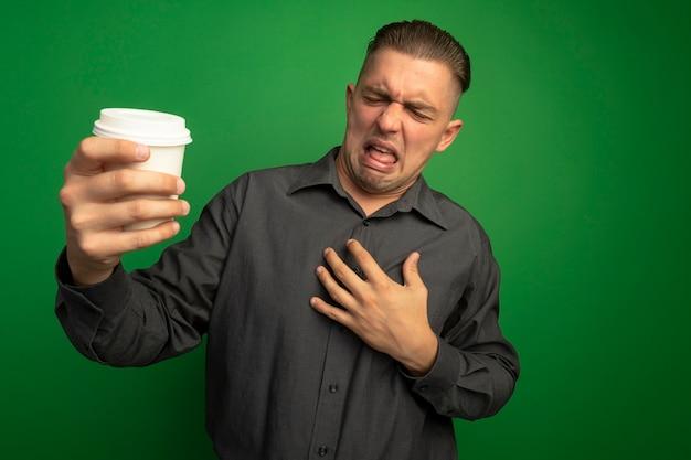 녹색 벽 위에 서있는 혐오 식으로 찾고 종이 컵을 들고 회색 셔츠에 젊은 잘 생긴 남자