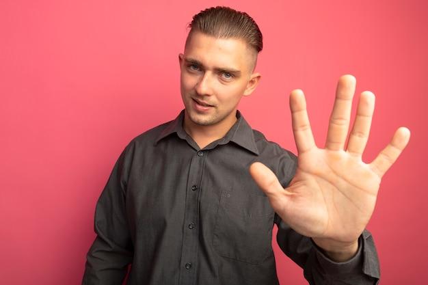 ピンクの壁の上に立っている番号5を示す自信を持って笑顔の正面を見て灰色のシャツを着た若いハンサムな男