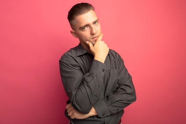 ピンクの壁の上に立っていると考えて彼のあごに手で正面を見て灰色のシャツの若いハンサムな男