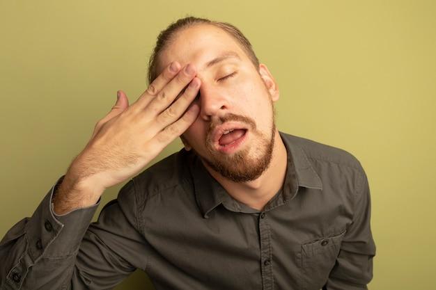 피곤하고 지루해 보이는 회색 셔츠에 젊은 잘 생긴 남자가 손으로 눈을 덮고 있습니다.