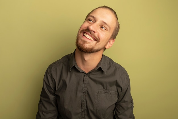 Молодой красавец в серой рубашке смотрит вверх, думая позитивно, широко улыбаясь