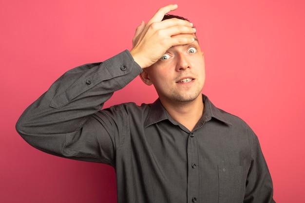 彼の額の上の手で心配して混乱しているように見える灰色のシャツを着た若いハンサムな男