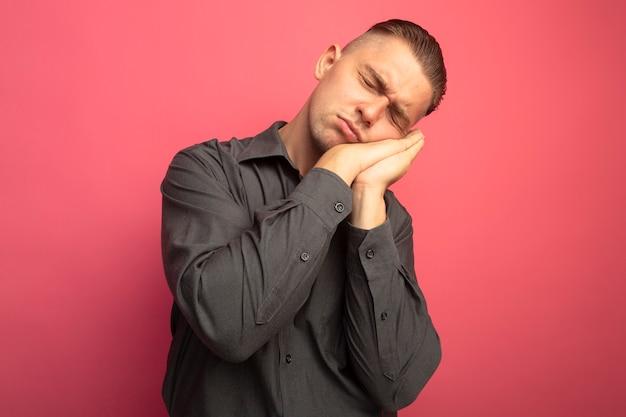 ピンクの壁の上に立っている彼の手のひらに頭を傾けて目を閉じて睡眠ジェスチャーをしている灰色のシャツの若いハンサムな男