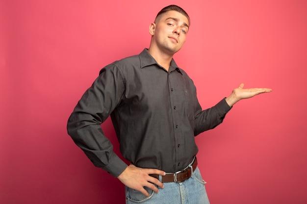 ピンクの壁の上に立って自信を持って見える彼の手の腕で何かを提示灰色のシャツを着た若いハンサムな男