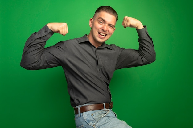 緑の壁の上に立っている上腕二頭筋と強さの勝者の概念を示す幸せでポジティブな拳を上げる灰色のシャツの若いハンサムな男