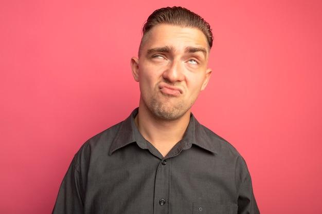 Молодой красавец в серой рубашке закатывает глаза, раздраженный и недовольный