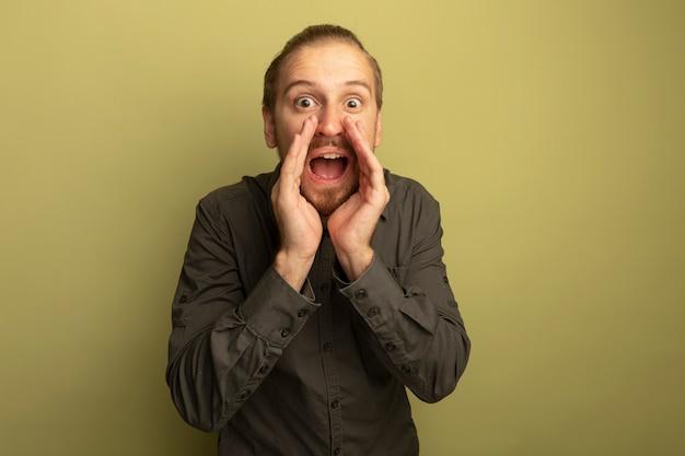 灰色のシャツを着た若いハンサムな男が驚いて見える口の近くの手で誰かを叫んだり電話したり