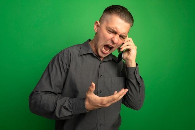 緑の壁の上に立っている携帯電話で話している間、攻撃的な表情で叫んでいる灰色のシャツの若いハンサムな男