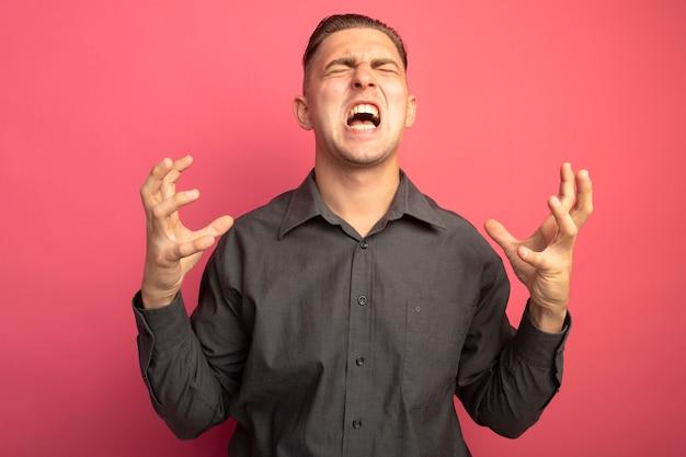 ピンクの壁の上に立って怒って狂った狂った腕を上げて叫んでいる灰色のシャツの若いハンサムな男