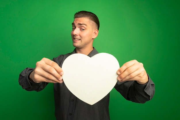 Молодой красавец в серой рубашке показывает картонное сердце, глядя на него с растерянным выражением лица