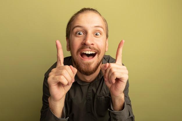 회색 셔츠에 젊은 잘 생긴 남자 놀라게하고 좋은 생각을 갖는 검지 손가락을 보여주는 행복
