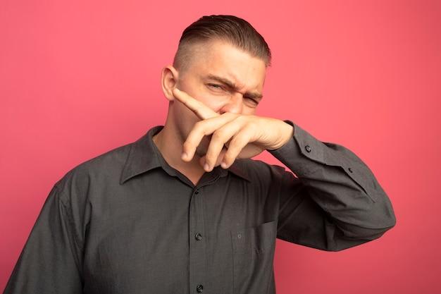ピンクの壁の上に立っている手で彼の鼻を拭く灰色のシャツの若いハンサムな男