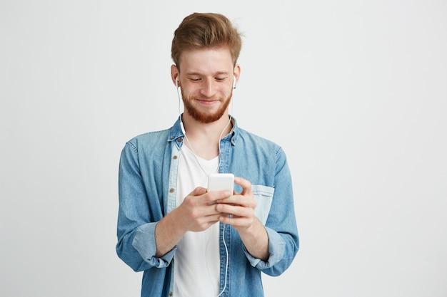 音楽のストリーミングを聞いて電話を見て笑ってヘッドフォンで若いハンサムな男。