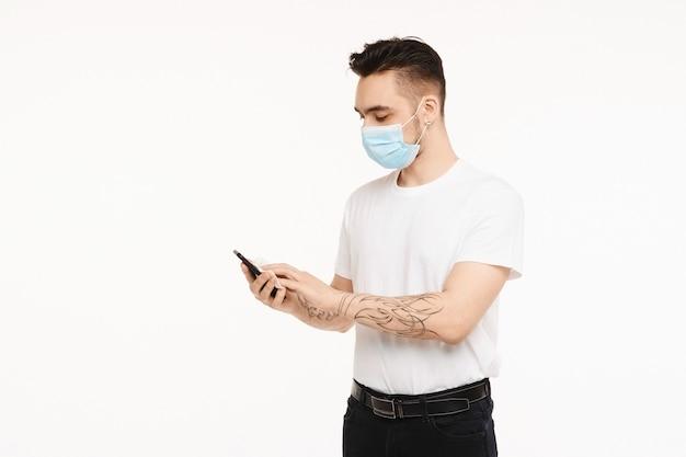 防護マスクの若いハンサムな男は彼の電話を抗菌ワイプできれいにします