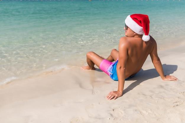 海の背景に後ろからサンタ帽子の若いハンサムな男