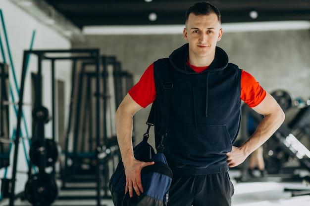 Молодой красавец в спортивной одежде в тренажерном зале