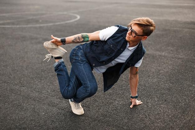 Молодой красавец в стильном джинсовом платье танцует хип-хоп