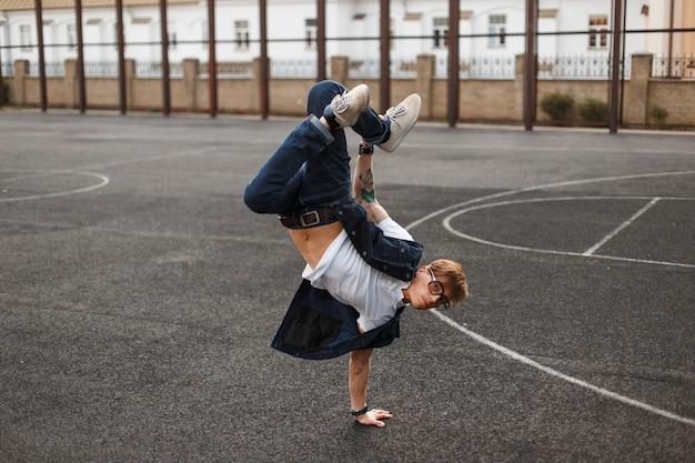 Молодой красавец в стильном джинсовом платье танцует на улице