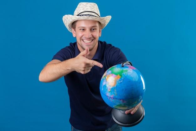 Молодой красавец в летней шляпе держит глобус, указывая пальцем на него, весело улыбаясь, стоя на синем фоне