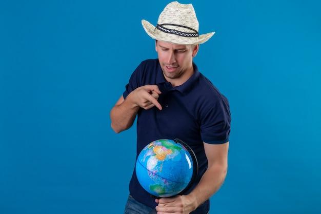 青い背景の上に元気に立って笑ってそれに指で指しているグローブを保持している夏帽子の若いハンサムな男