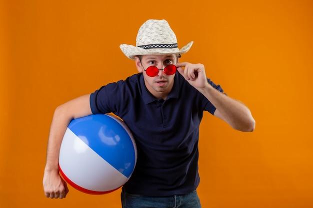 Молодой красавец в летней шляпе держит надувной мяч, глядя в камеру, снимая очки, глядя в камеру, удивленный и заинтригованный, стоя на оранжевом фоне
