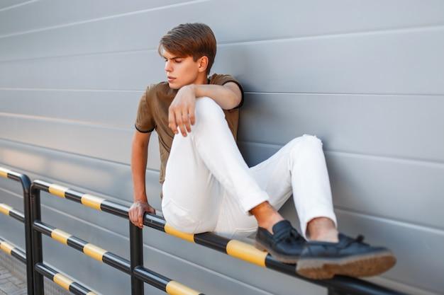 금속 벽 근처에 앉아 유행 세련된 옷을 입고 젊은 잘 생긴 남자