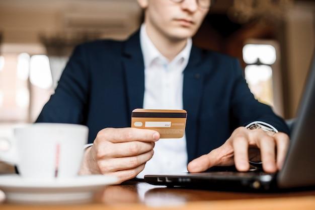 若いハンサムな男は、美しいレストランでクレジットカードとラップトップを使用してオンラインで購入しています。