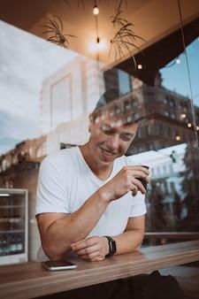 若い、ハンサムな男は、カフェで彼の朝のコーヒーを飲んでいます。