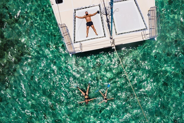 A young handsome man is lying on a yacht in the indian ocean next to his family swimming in masks.mauritius island.