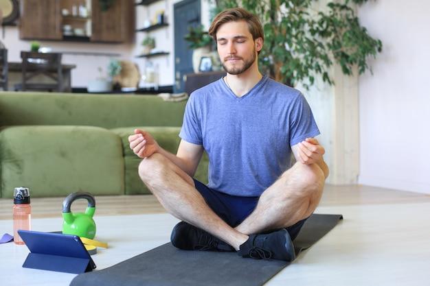 若いハンサムな男は、検疫中に自宅の床に座って蓮華座でヨガを練習しています。スポーツは健康的な生活の基盤です。