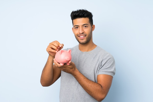 Young handsome man over isolated background holding a big piggybank