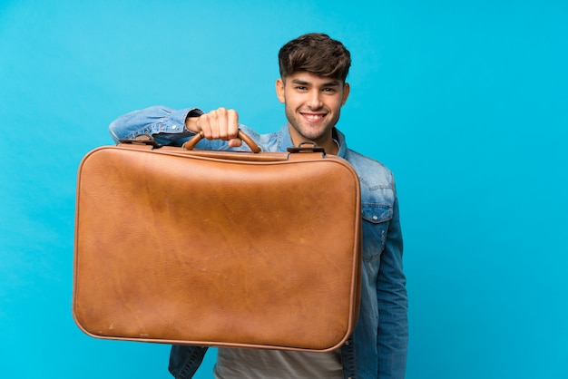 Young handsome man over isolated blue holding a vintage briefcase