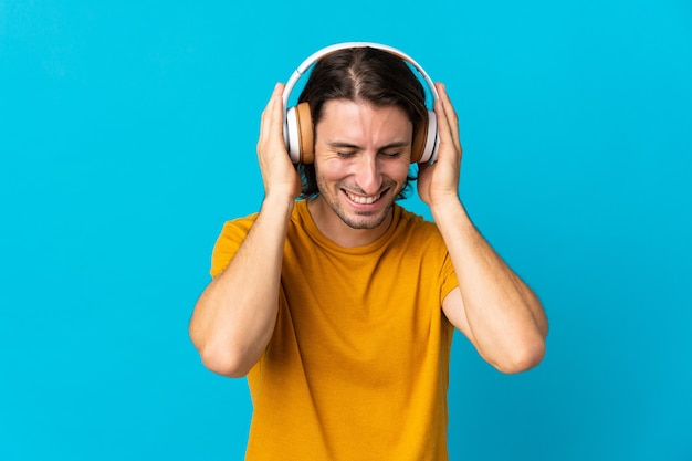 Young handsome man isolated on blue listening music