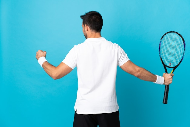 Young handsome man isolated on blue wall playing tennis and celebrating a victory