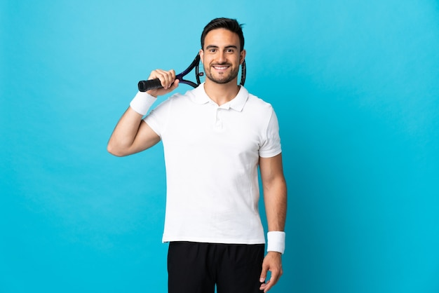 Young handsome man isolated on blue wall playing tennis