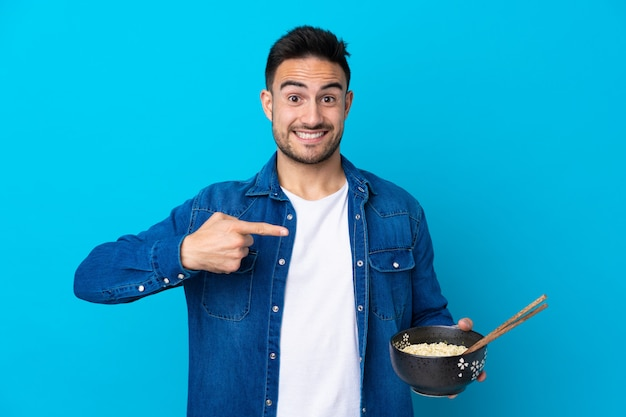 Young handsome man over isolated blue wall and pointing it while holding a bowl of noodles with chopsticks