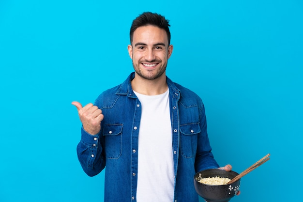 Young handsome man over isolated blue wall pointing to the side to present a product while holding a bowl of noodles with chopsticks