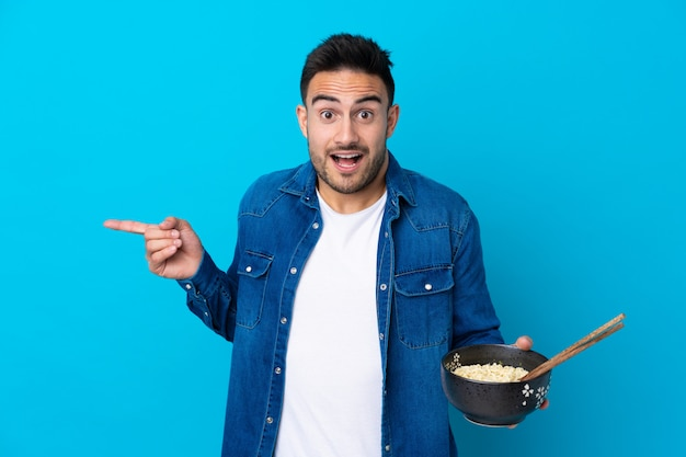 Young handsome man over isolated blue wall surprised and pointing finger to the side while holding a bowl of noodles with chopsticks