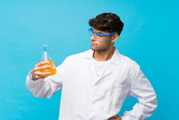 Young handsome man over isolated blue with a scientific test tube