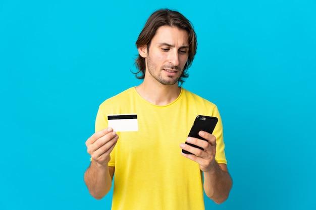 クレジットカードで携帯電話で購入する青い背景に孤立した若いハンサムな男