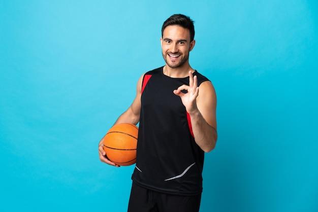 バスケットボールをし、okサインを作る青い背景で隔離の若いハンサムな男