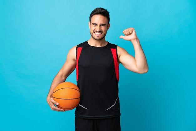 バスケットボールをしている青い背景に孤立し、彼自身を誇りに思っている若いハンサムな男