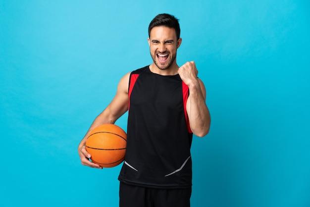 バスケットボールをしている青い背景に分離された若いハンサムな男