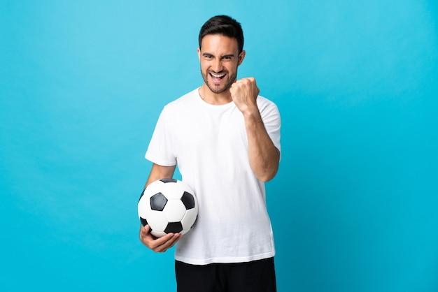 승리를 축 하하는 축구 공 파란색 배경에 고립 된 젊은 잘 생긴 남자